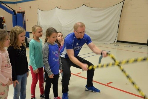 AES Physical Education teacher Adam Davidson works with students during PE class.