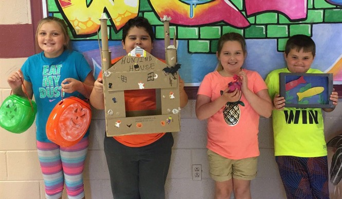 The students in Ms. Mindie Anderson's 3rd grade class at AES show off their recycle projects.