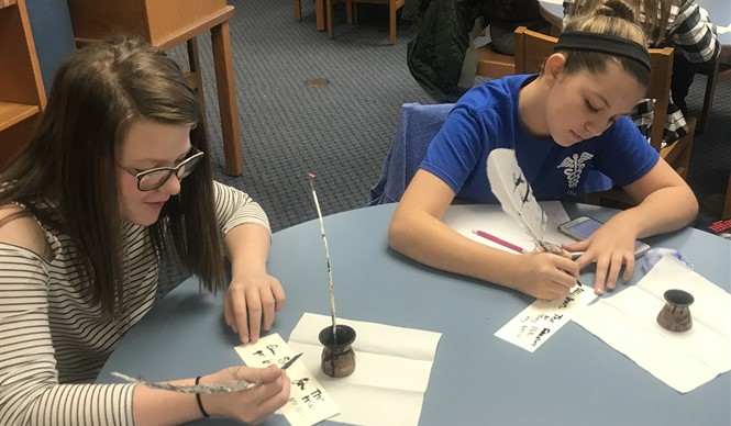 Students write bills with quill pens during a History smArts outreach program with the Kentucky Historical Society.